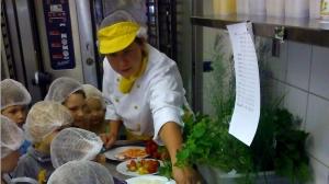 Mittendrin im Gemüse-Obst-Kräuterquiz: RWS-Köchin Christin Rokosch mit einer Kindergartengruppe.